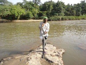 Professor O.O. Oyesiku waiting to cross a river with crocodiles